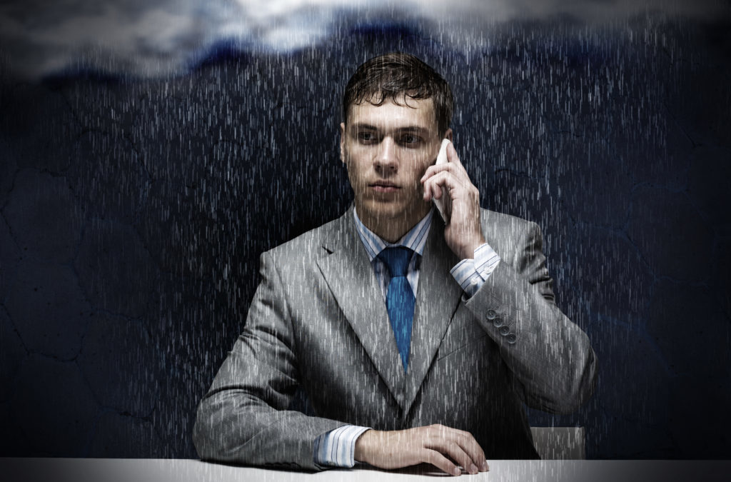 Un hombre está hablando por teléfono mientras cae lluvia, representando los comentarios negativos sobre su empresa