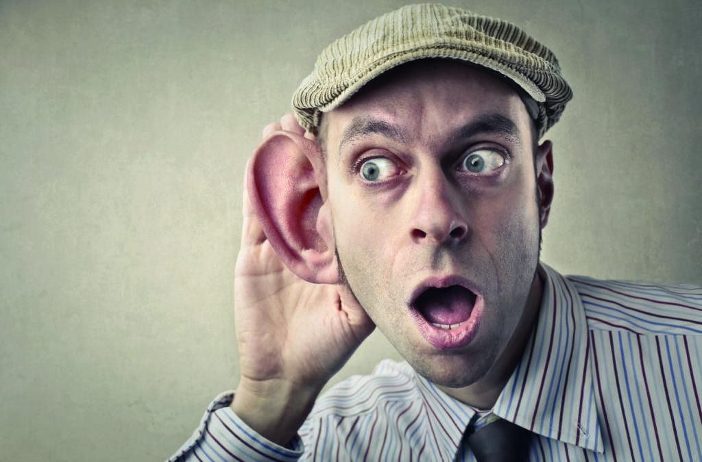 Un hombre escucha con una oreja enorme