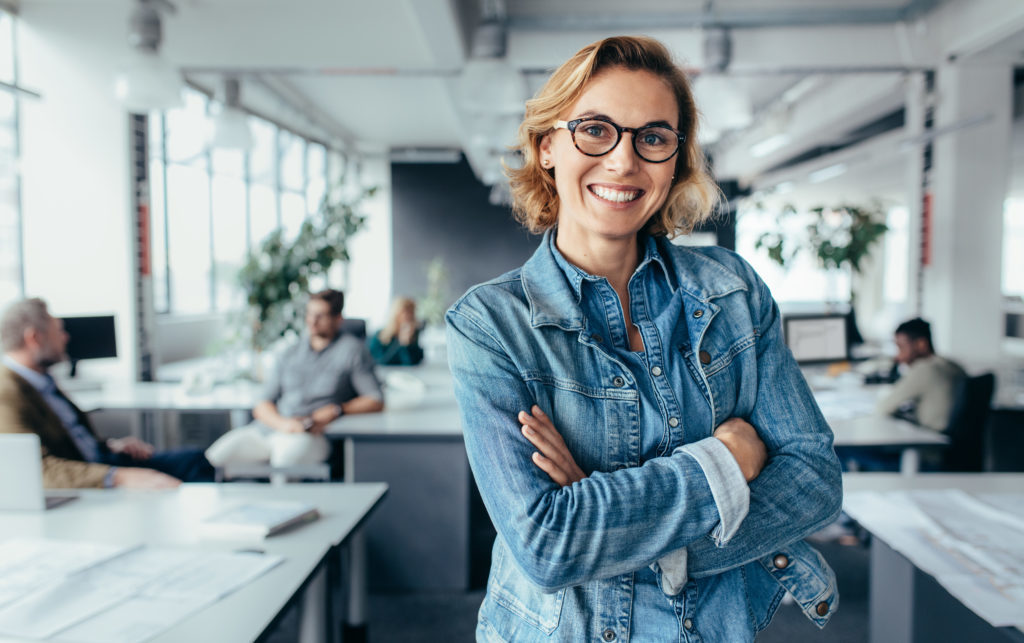 Una mujer sonriente mira a la cámara desde su oficina. En el fondo se ve a sus compañeros de trabajo sobre sus mesas