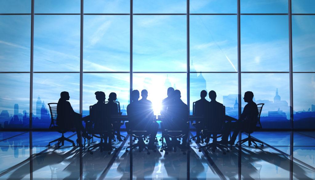 Una serie de personas están sentadas y reunidas en una gran mesa delante de un gran ventanal