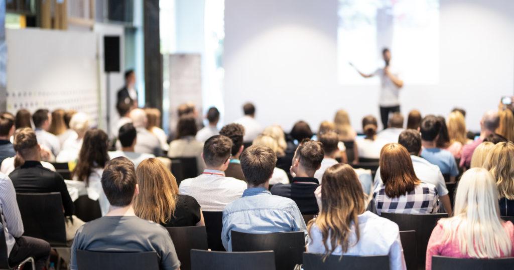 Una sala llena de gente que escucha a un ponente dando un discurso