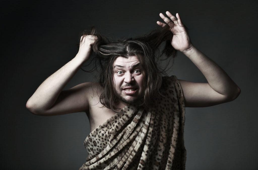 Un hombre vestido de cromañón se tira de los pelos