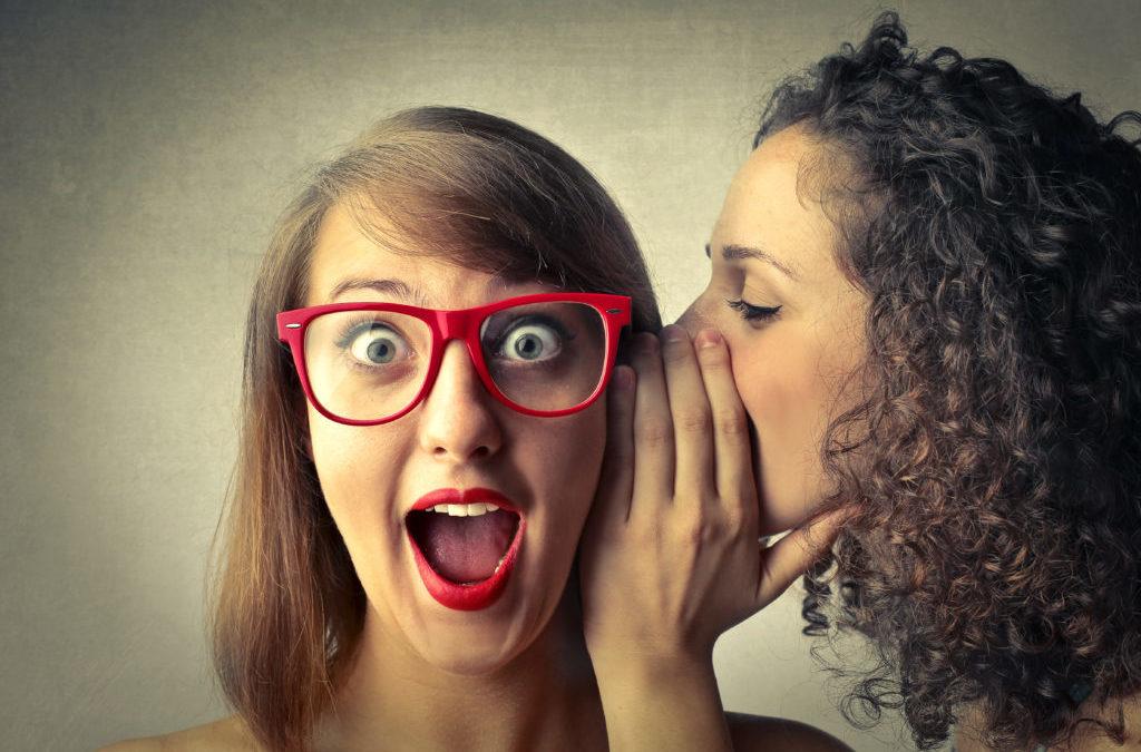 Una chica cuenta a un secreto a otra que pone cara de sorpresa