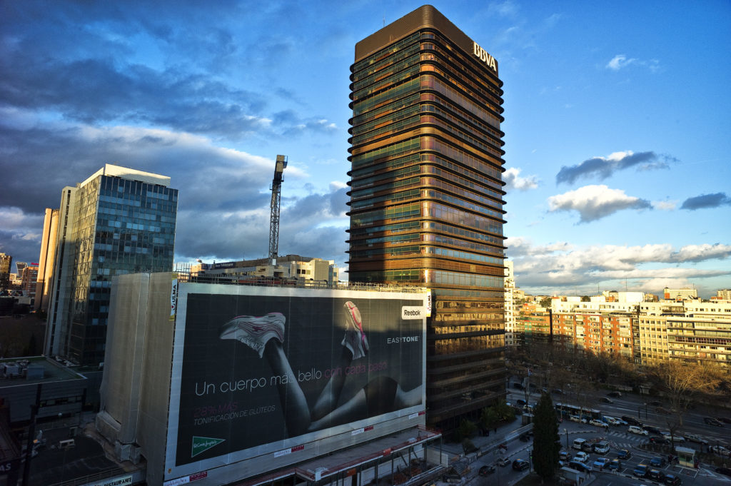 En la foto se ve un gran cartel al lado del edificio BBVA de la Gran Vía de Madrid