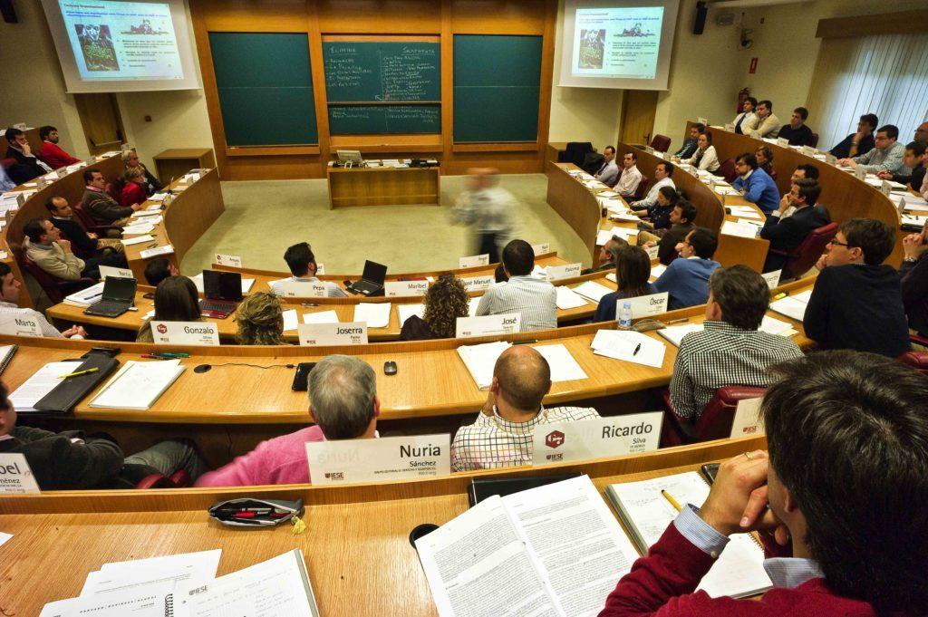 En la foto se ve un aula de universidad llena de personas que acuden a una conferencia