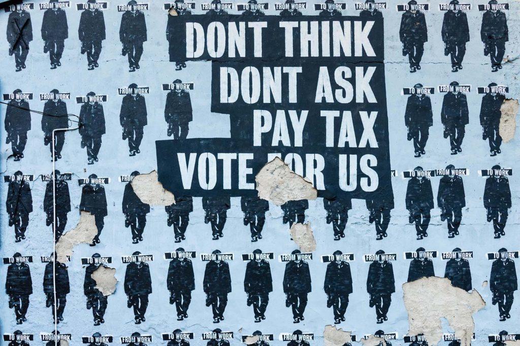 En la foto se ve una pared forrada de carteles de protesta por los impuestos
