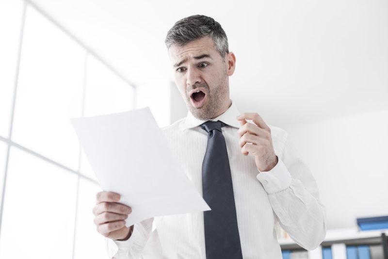 En la foto se ve a una persona que mira un papel y al verlo se asusta