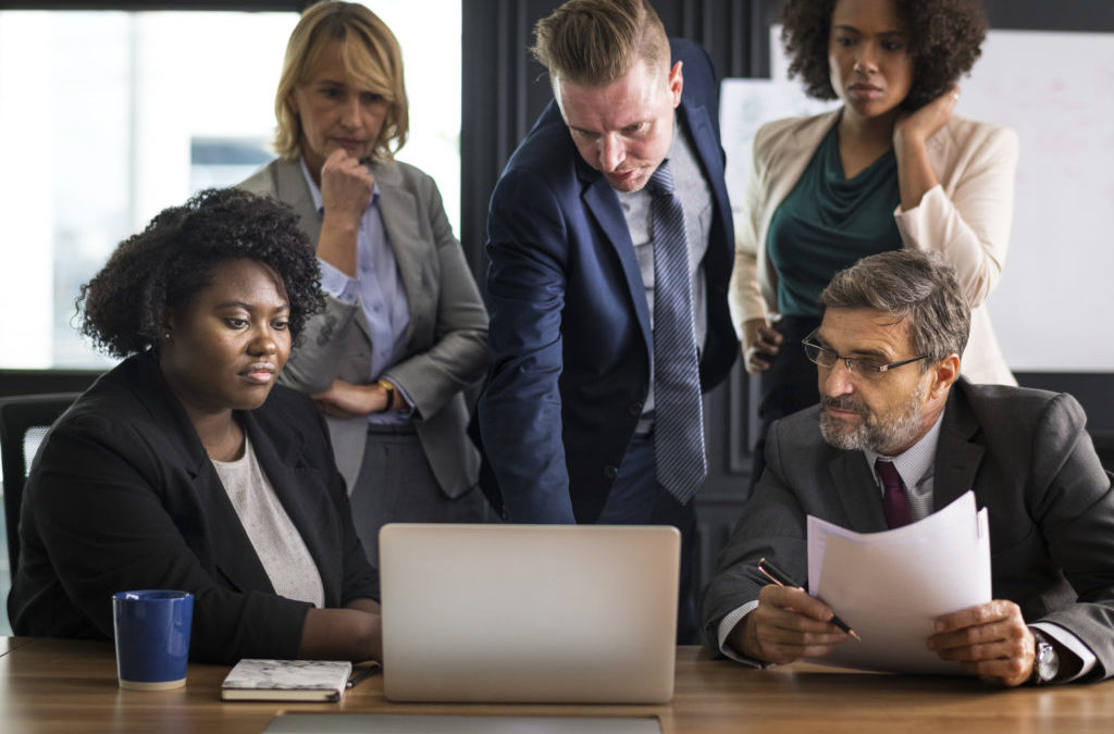 En la foto se ve a un equipo de trabajo mirando un ordenador y haciendo una puesta en común