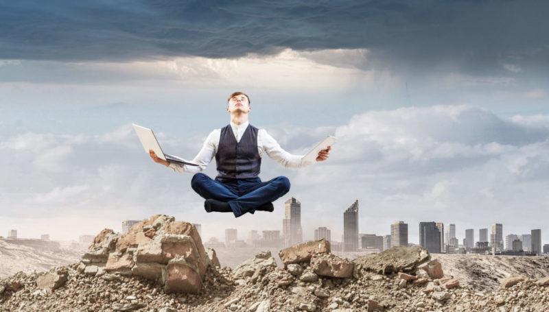 Foto de una ciudad destruida y llena de escombros en la que en medio se ve a un hombre que medita y está levitando con un ordenador en una mano y un ipad en la otra