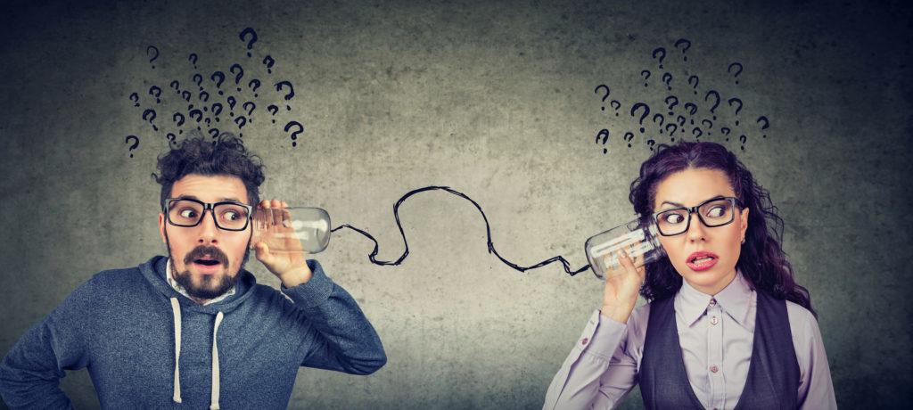 Un hombre y una mujer intentan hablar por medio de dos vasos conectados con un hilo