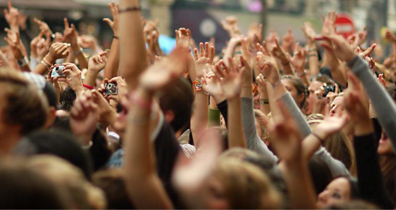 En la foto se ve a una masa de personas levantando las manos