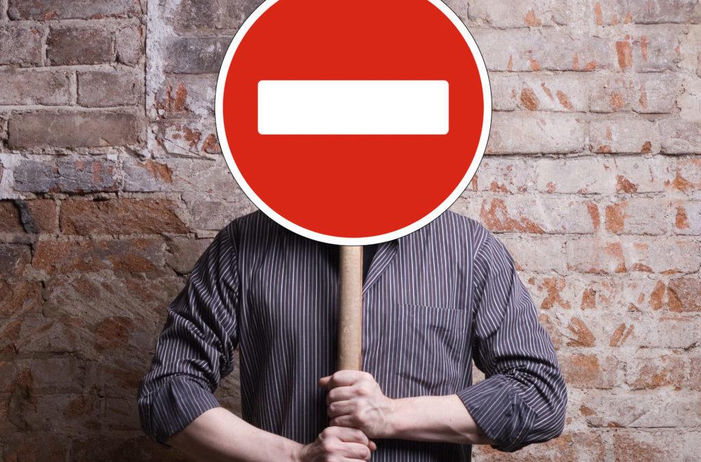 """En la foto aparece un hombre que se tapa la cara con la señal de """"prohibido"""" que sujeta entre las manos"""