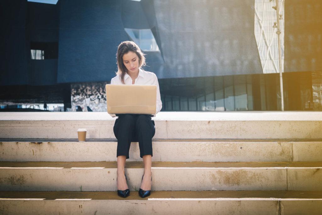 En la foto se ve a una chica sentada en unas escaleras trabajando en su ordenador