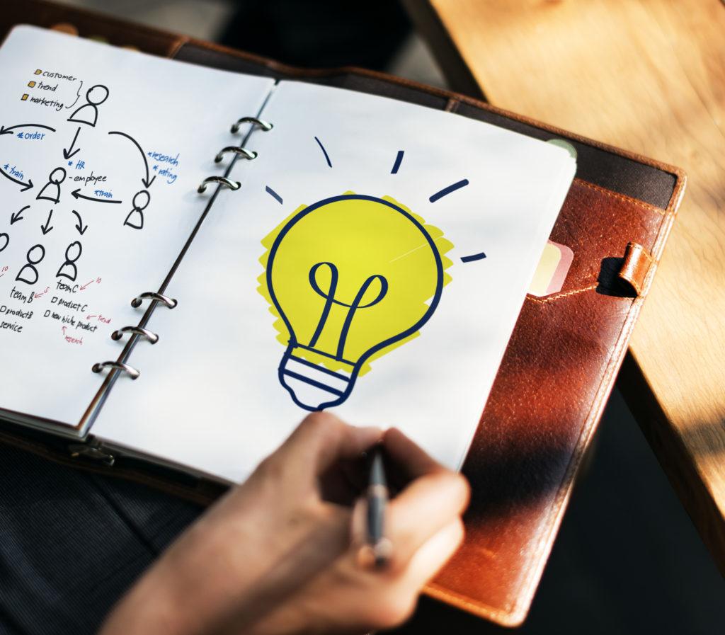 En la foto se ve a una persona que está dibujando una bombilla en su libreta, en representación de haber tenido una buena idea