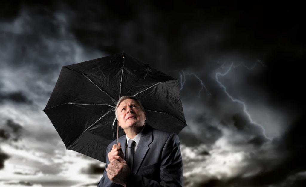 En la foto aparece un hombre con un paraguas en medio de una tormenta eléctrica