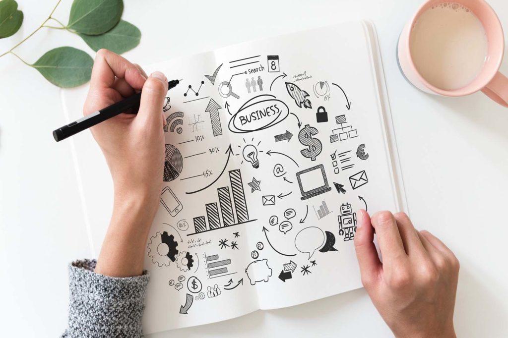 En la foto se ve a una persona que escribe y dibuja en su libreta para planificar su campaña de marketing