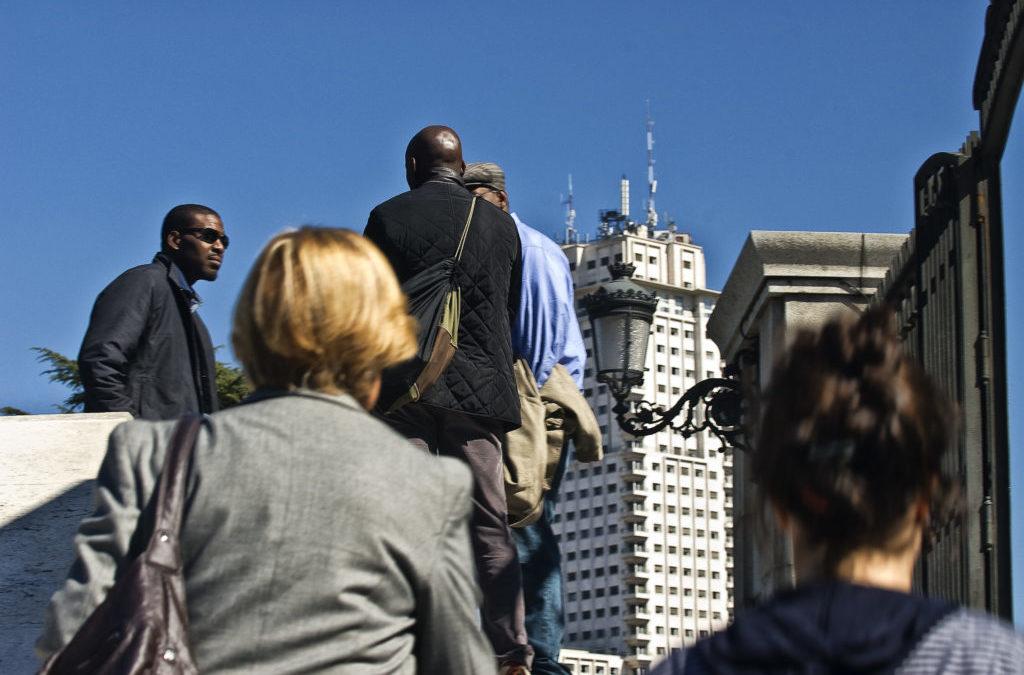 En la foto se ven varias personas que salen de la boca del metro