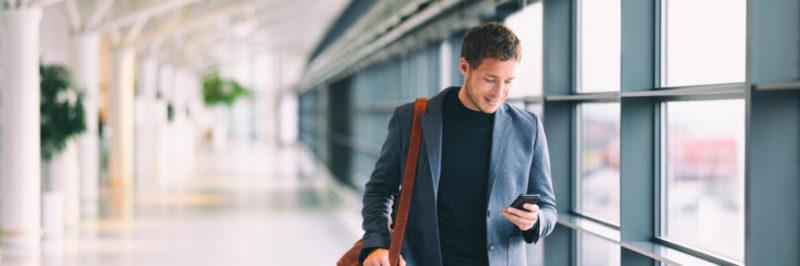 Un hombre mira su teléfono en medio de un aeropuerto