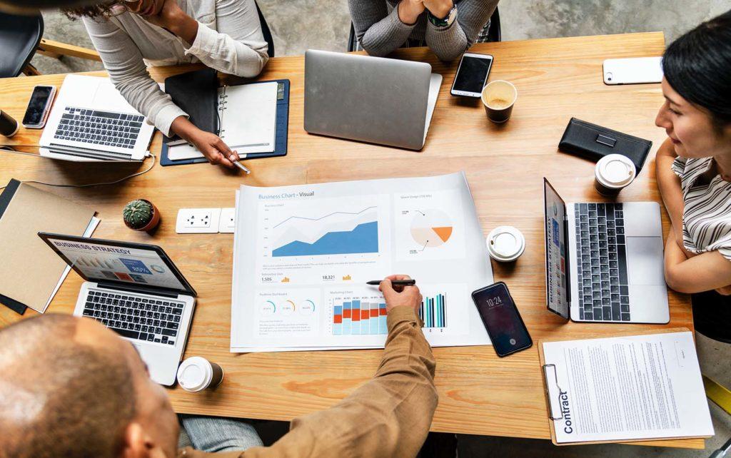 En la foto se ve a un grupo de personas sobre una mesa que están mirando un papel en el que salen gráficas y estadísticas sobre su empresa