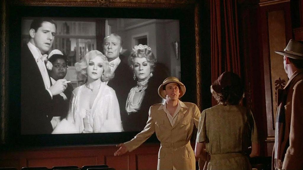 En la foto se ve a tres personas que discuten delante de una pantalla de cine en la que se ve una foto en blanco y negro