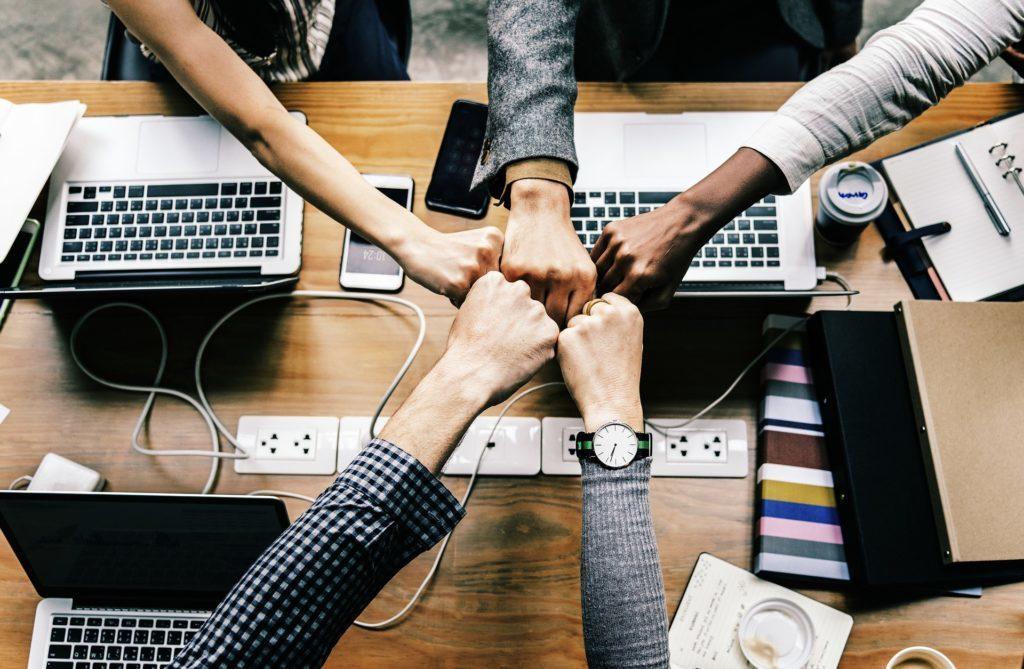 En la foto se ven los puños de cuatro personas, que se están juntando, como símbolo de trabajo en equipo